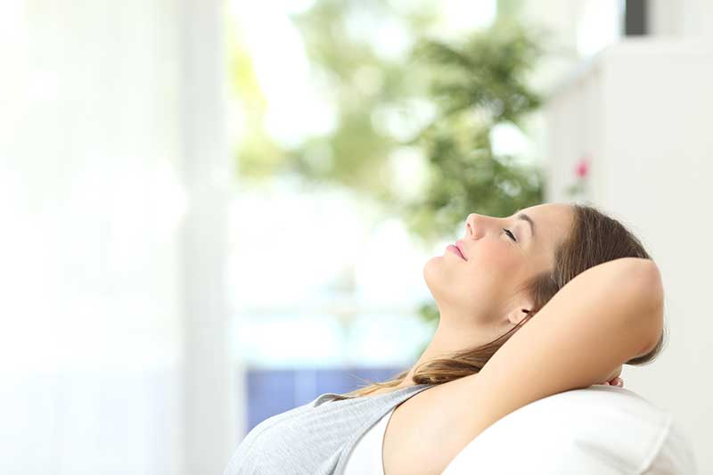 Woman smiling as she lays back and relaxes from the effects of sedation dentistry