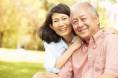 An older couple sitting in the park and smiling to show how Porcelain Bridges can safely and permanently replace missing teeth.