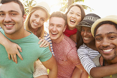 A group of young people laughing and smiling illustrates how our Seattle Family Dentistry can keep your smile healthy through safe and effective gum laser therapy.