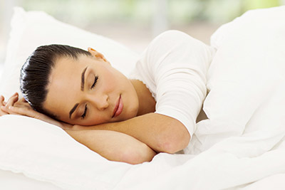 A woman sleeping on a white bed illustrates that our Sand Point area dentist uses Sedation Dentistry to help patients with anxiety.