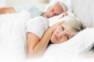 A woman is unable to sleep because of her snoring husband who is in need of Sleep Apnea treatment.