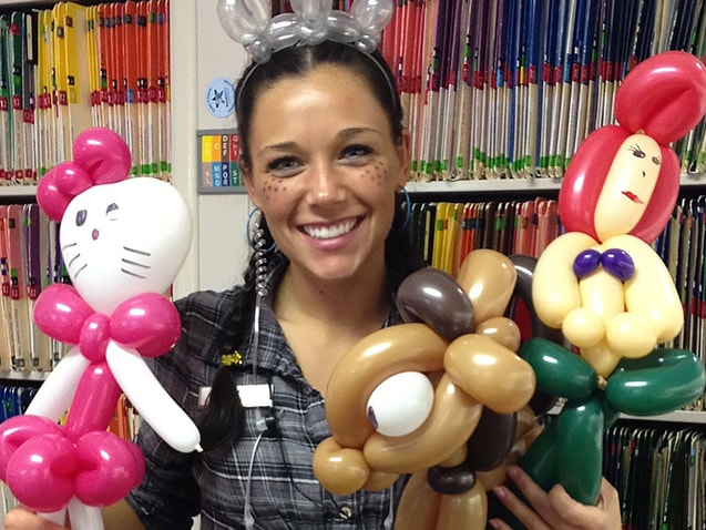 Dental team member with balloon animals and face paint