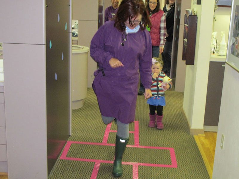 Dr. Vicki Fidler a Seattle dentist, playing hop scotch with a younger patient