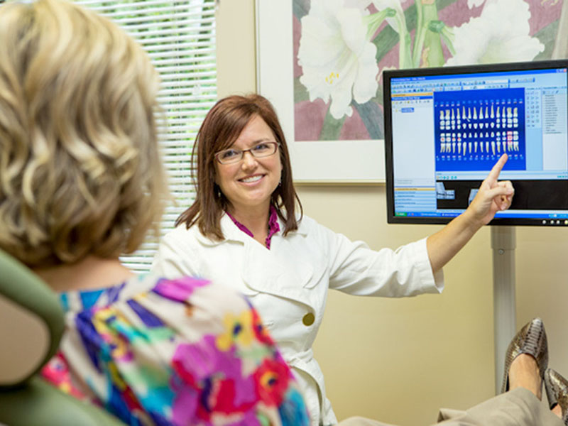 Dr. Vicki Fidler, a Seattle dentist, talking to a patient while pointing to a computer screen