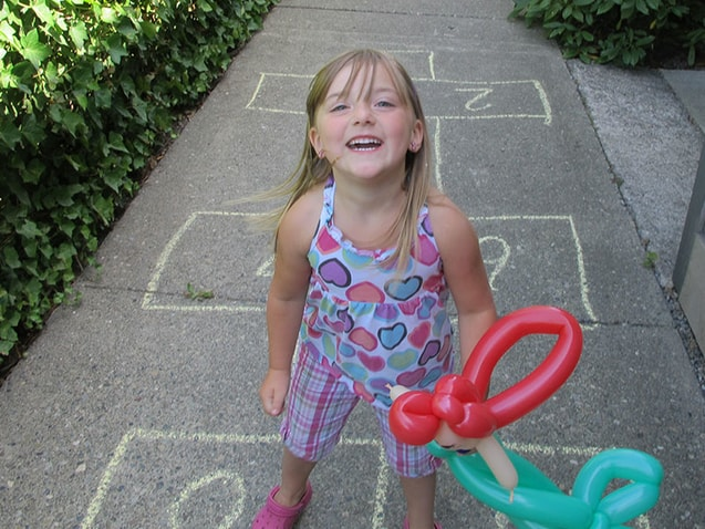 Little girl outside with balloon animal on sidewalk