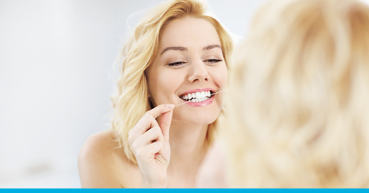 A blonde woman flossing her teeth