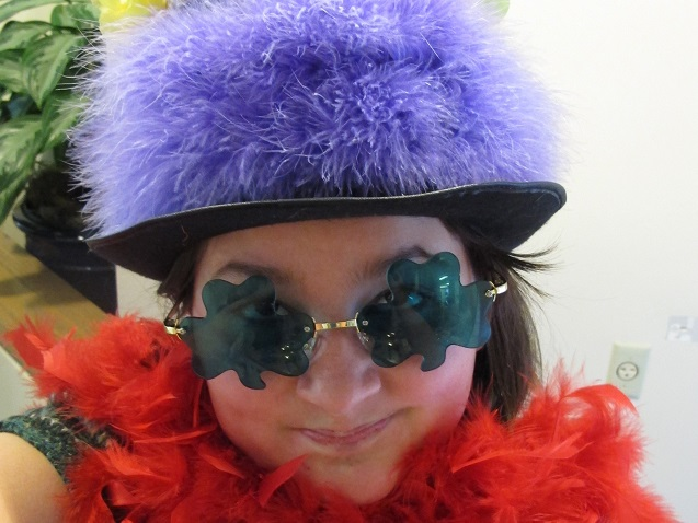 Selfie of girl in glasses with purple feathered hat.
