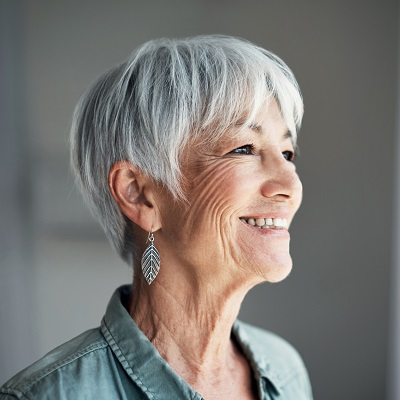 Older woman smiling and laughing to illustrate how dental implants can restore your smile.