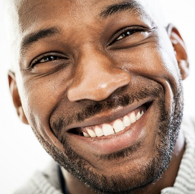 Smiling man with beautiful white teeth with metal-free fillings.