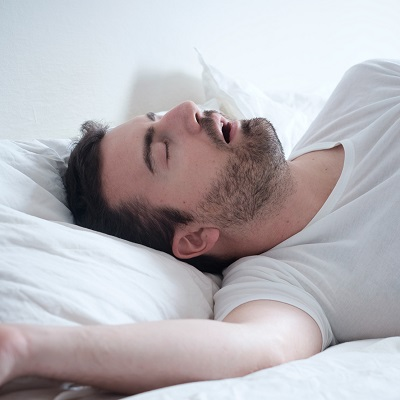 Man sleeping in his bed and snoring loudly because of sleep apnea.