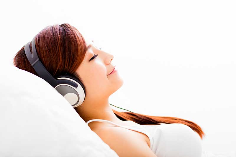 Young woman laying back and listening to music to ease her dental anxiety