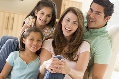 A family sitting on the couch together smiling to illustrate the importance of routine dental cleanings.