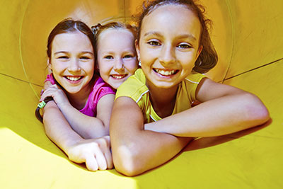 Three young girls playing at a playground smile to show how metal-free fillings keep your smile looking natural.