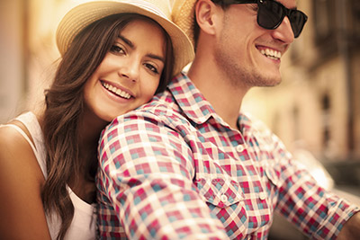 A Smiling couple shows how Invisalign custom aligners can give you a straighter smile more discreetly than traditional braces.