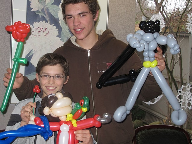 Two boys smiling with balloons