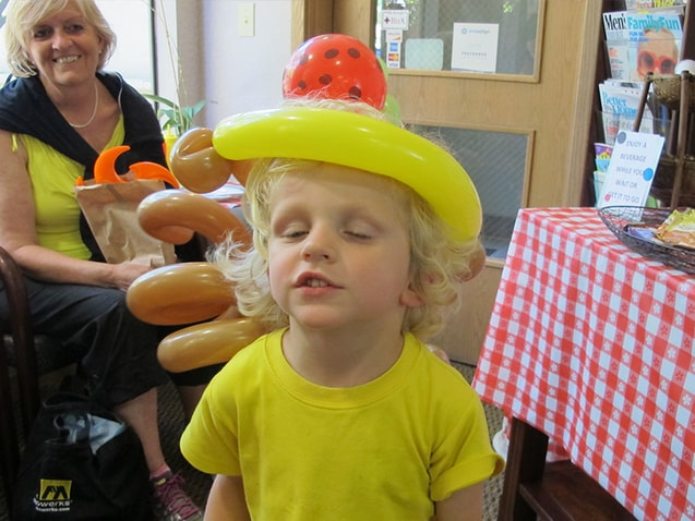 Young boy in yellow with fun balloon hat